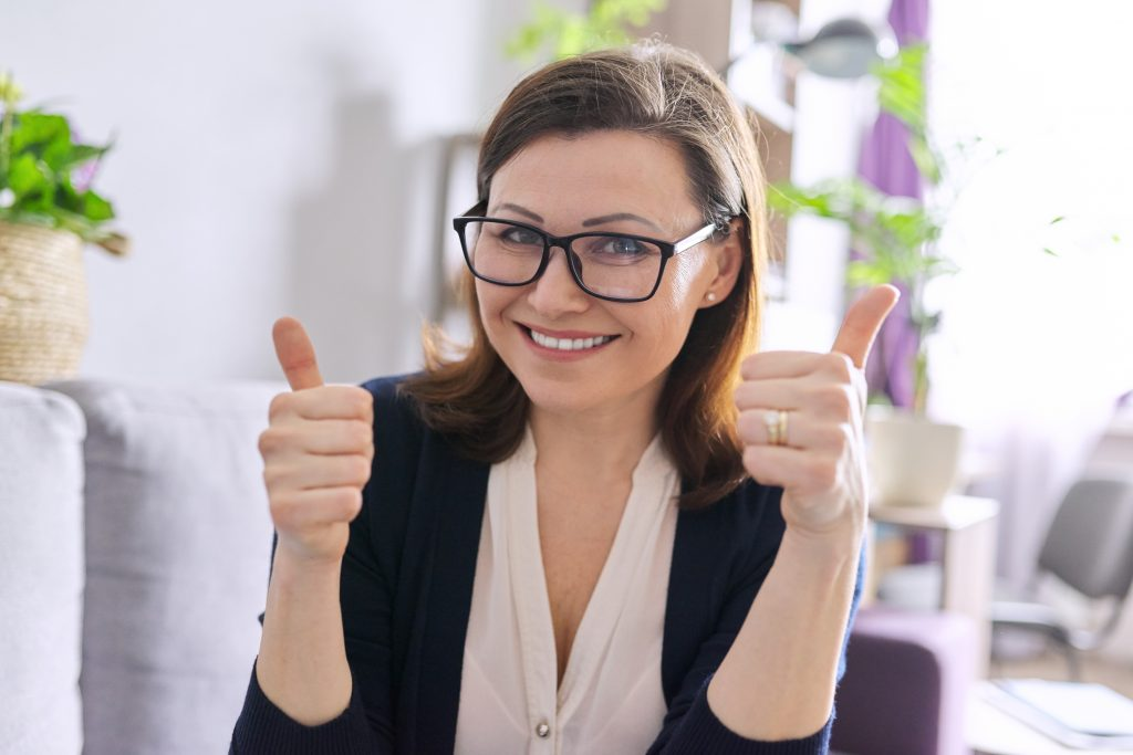 business woman looking at webcam, engaging with client colleagues, shows thumbs up hand sign